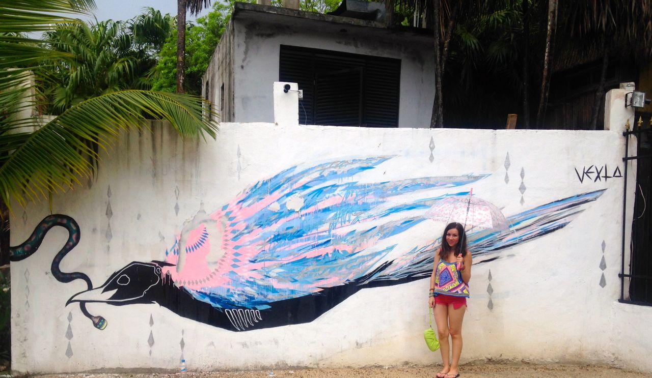 Nihan Gorkem posing in front of a bird mural in Tulum Mexico