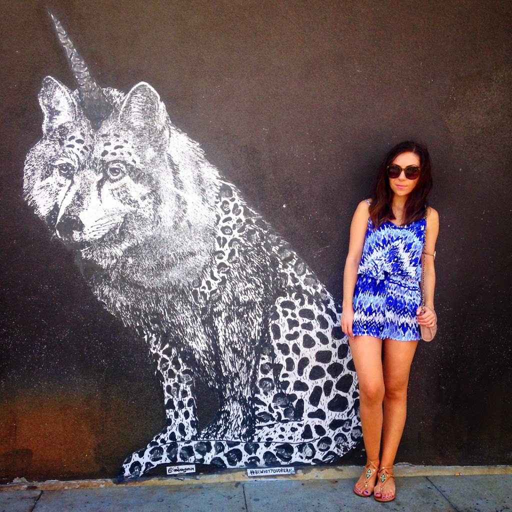 Blogger Nihan posing with the unicorn wolf cheetah mural in venice beach Los Angeles and showing her outfit, a blue iilim print romper