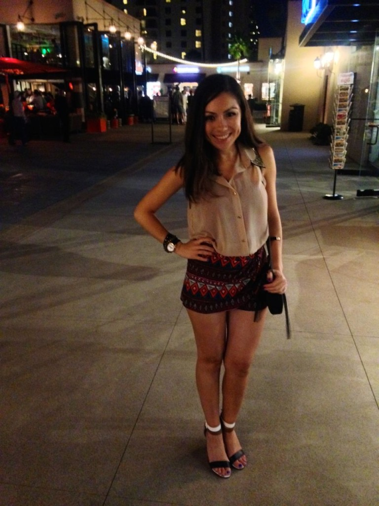 Blogger Nihan wearing an aztec printed mini shorts,  a neutral top and fun sandals while posing in Seaport Village San Diego