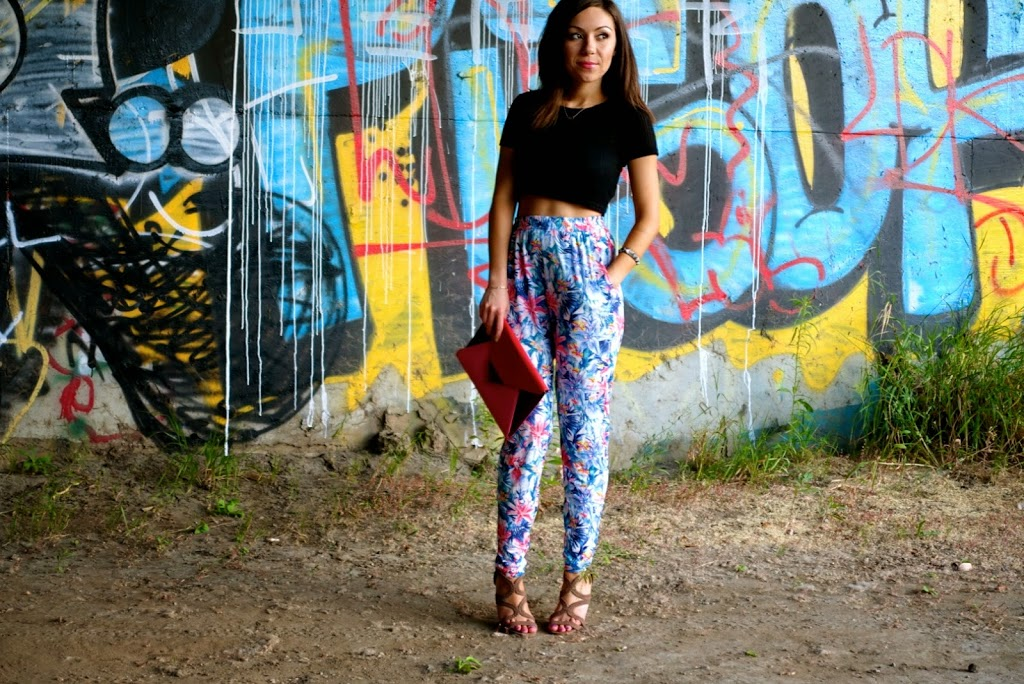 Blogger Nihan posing in front of a graffiti wall, wearing floral print harem pants, black crop top and high-heels