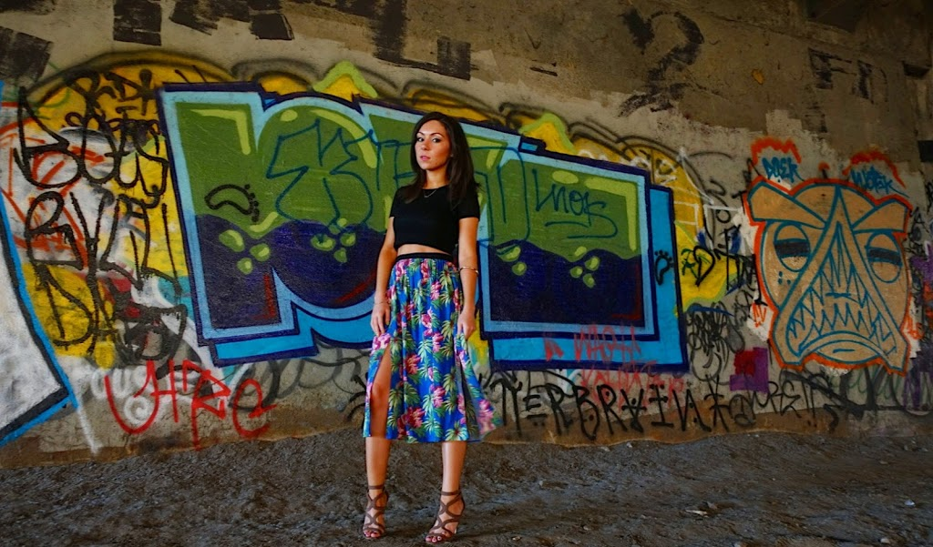 Blogger Nihan posing in front of a graffiti wall and showing her outfit: a floral midi skirt by Topshop and a black crop top