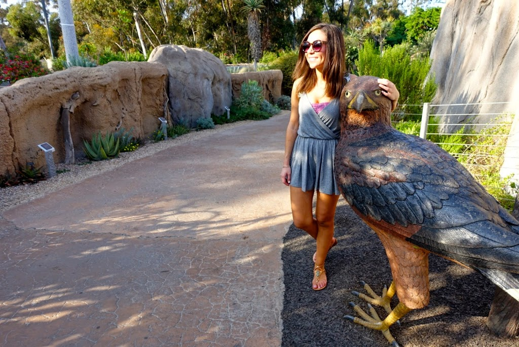 Blogger Nihan posing with a bird sculpture and showing her outfit, a casual grey romper at the San Diego Zoo