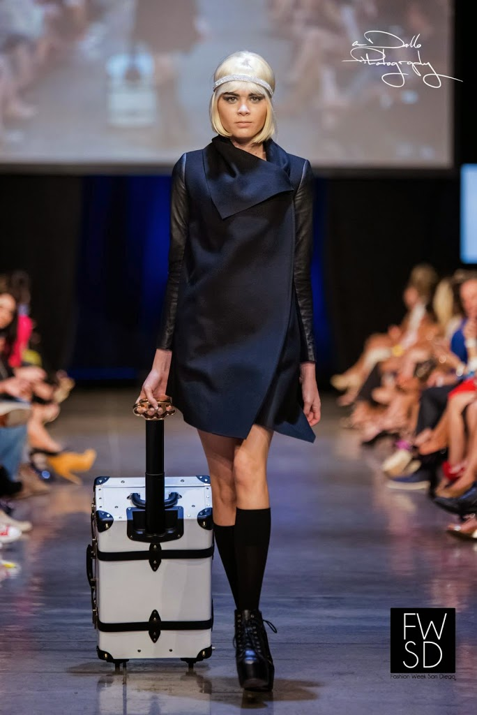 Model carrying a chic and elegant white luggage, walking down the runway