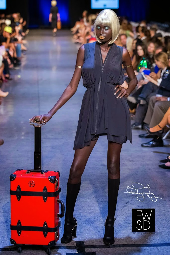 Model carrying a luggage and walking down the runway on Fashion Week San Diego 2014 Night 3