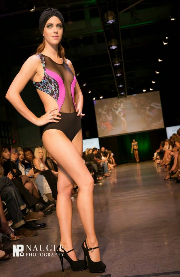 Model wearing a black mesh top and pink bikini bottoms walking down the runway during Fashion Week San Diego 2014 Night 3
