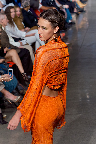 Model in orange dress walking down the runway on Fashion Week San Diego 2014 Night 2