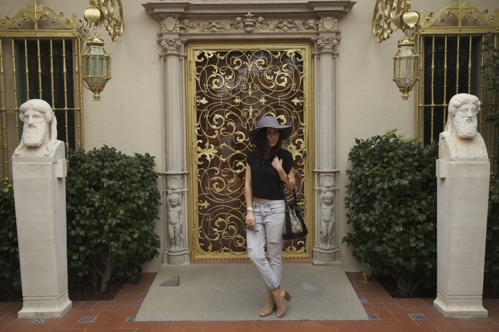 Blogger Nihan wearing gray Floppy Hat, ripped jeans and Topshop Duffel Bag while visiting Hearst Castle