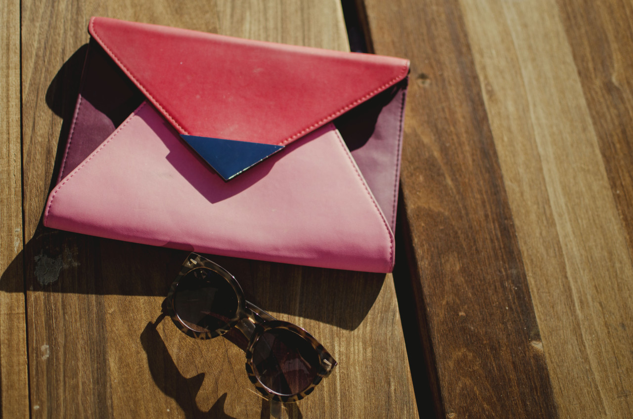 Blogger Nihan's festive, fun and trendy pink and red color block clutch and round sun glasses