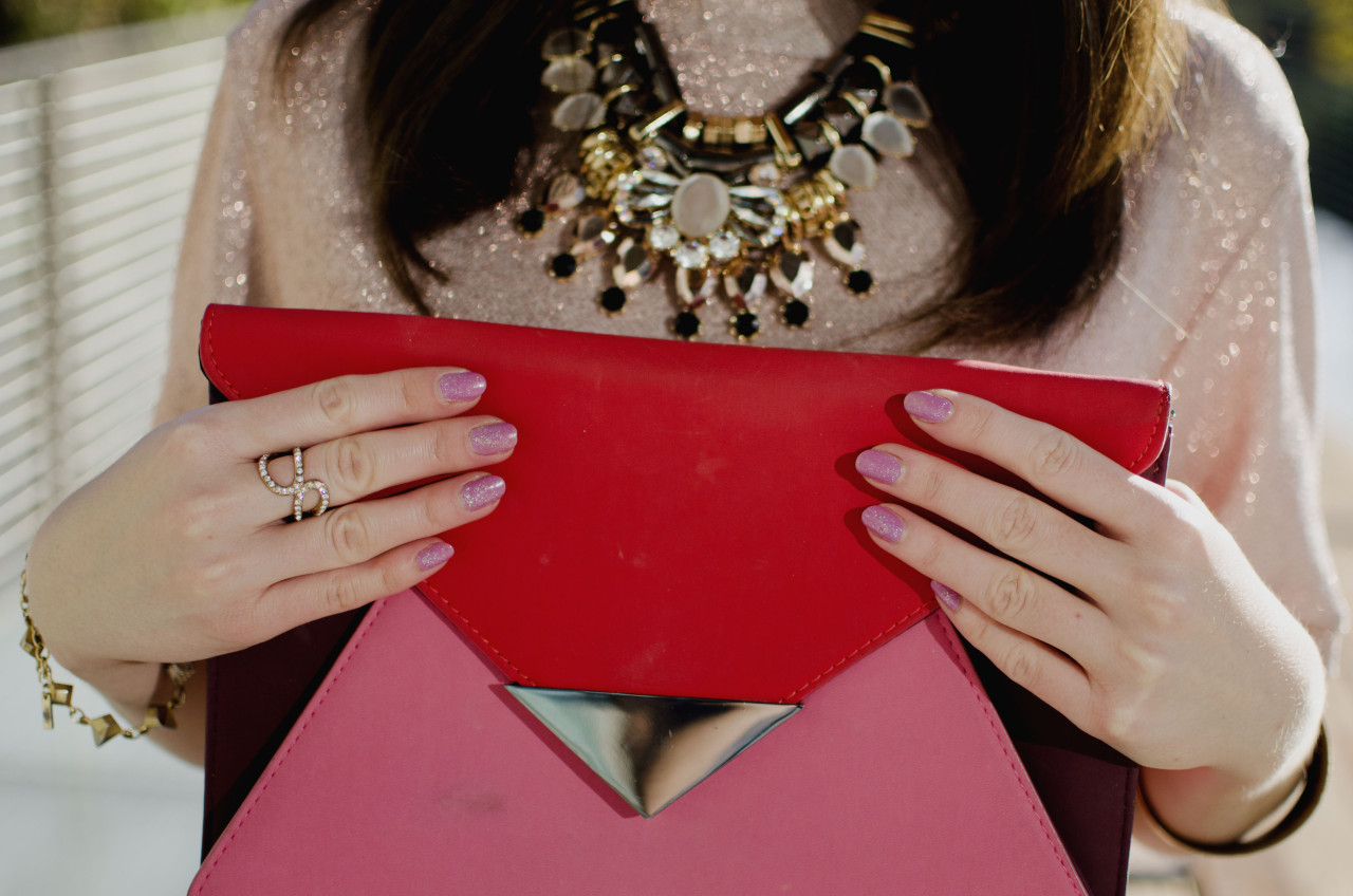 Blogger Nihan showing her rings, pink glittery nails and pink and red color block festive clutch