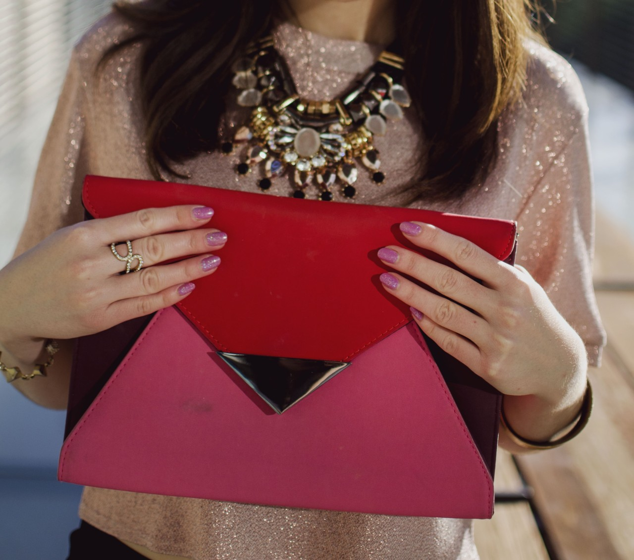 elegant holiday party look - Blogger Nihan showing her rings, necklace, pink glittery nails and pink and red color block festive clutch
