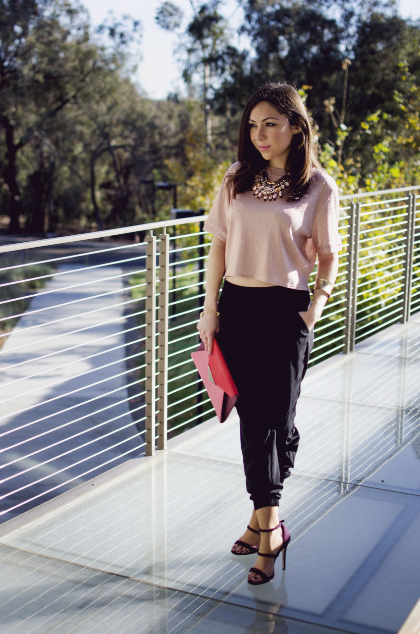 elegant holiday party look - Blogger Nihan standing and showing her Holiday Party Outfit; a pink metallic top, a big statement necklace, black jogger pants, maroon highly and a color block clutch.