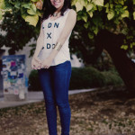 Nihan posing under a yellow big tree an showing her white t-shirt, jeans and boots
