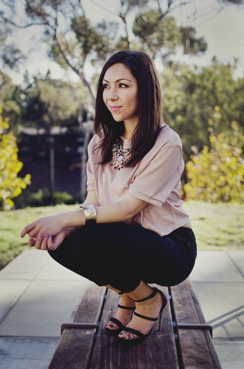 Blogger Nihan sitting and showing her Holiday Party Outfit; a pink metallic top, a big statement necklace, black jogger pants, maroon high heels and trendy jewelry.
