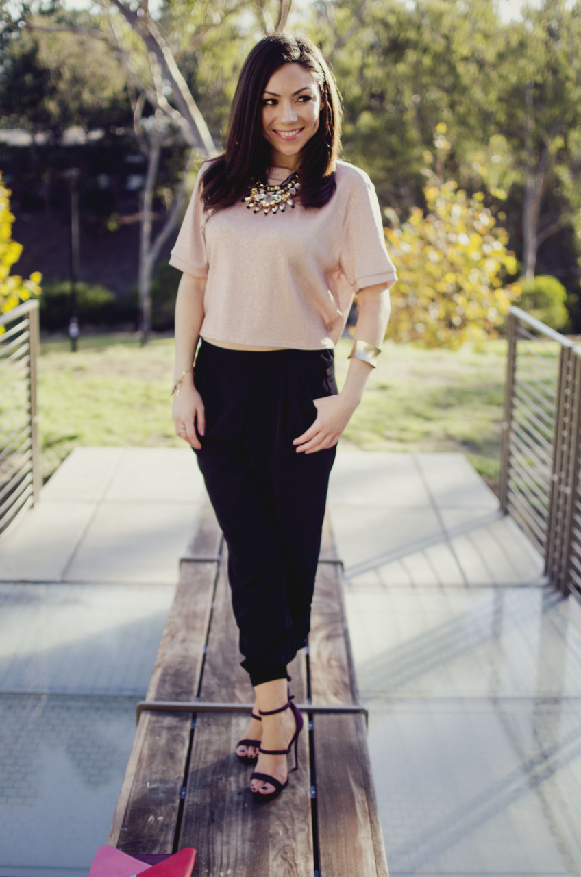 Blogger Nihan standing and showing her Holiday Party Outfit; a pink metallic top, a big statement necklace, black jogger pants, maroon highly and a color block clutch.