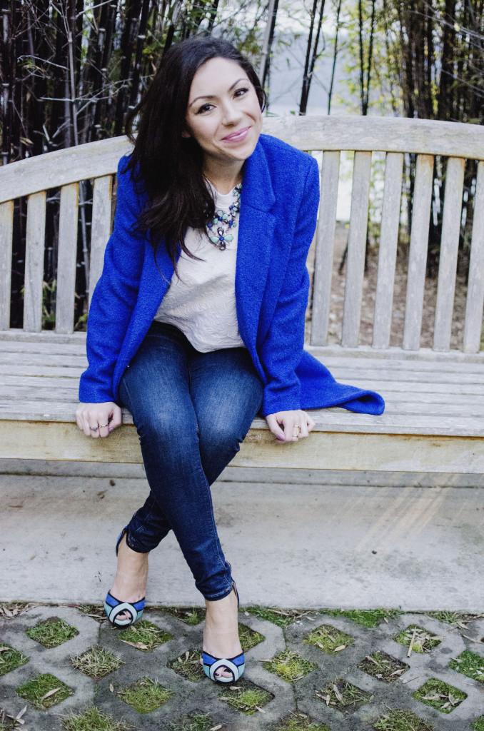 Fashion model smiling and showing her outfit featuring a blue oversized coat, white top, floral green and blue necklace and and Topshop jeans while sitting on a bench
