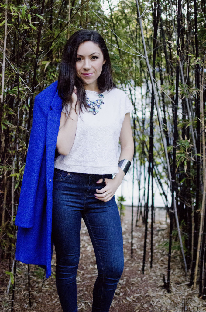 Fashion model wearing a cobalt blue coat and standing