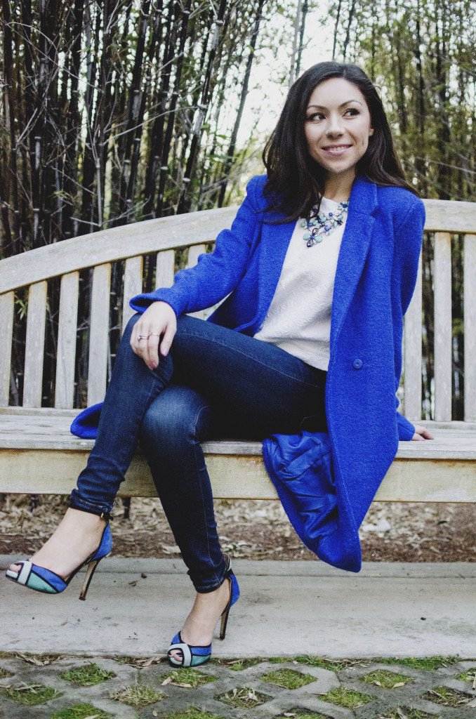 Nihan wearing a cobalt blue coat and posing while sitting on a bench