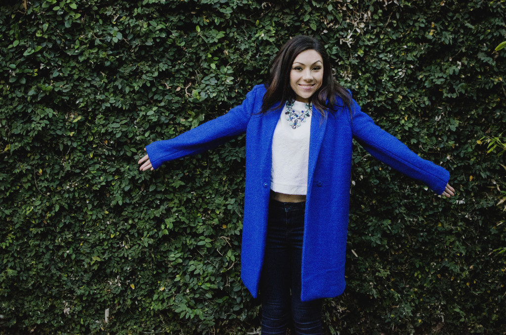 Fashion model being goofy and funny while showing her outfit featuring a blue oversized coat, white top, floral green and blue necklace and and Topshop jeans