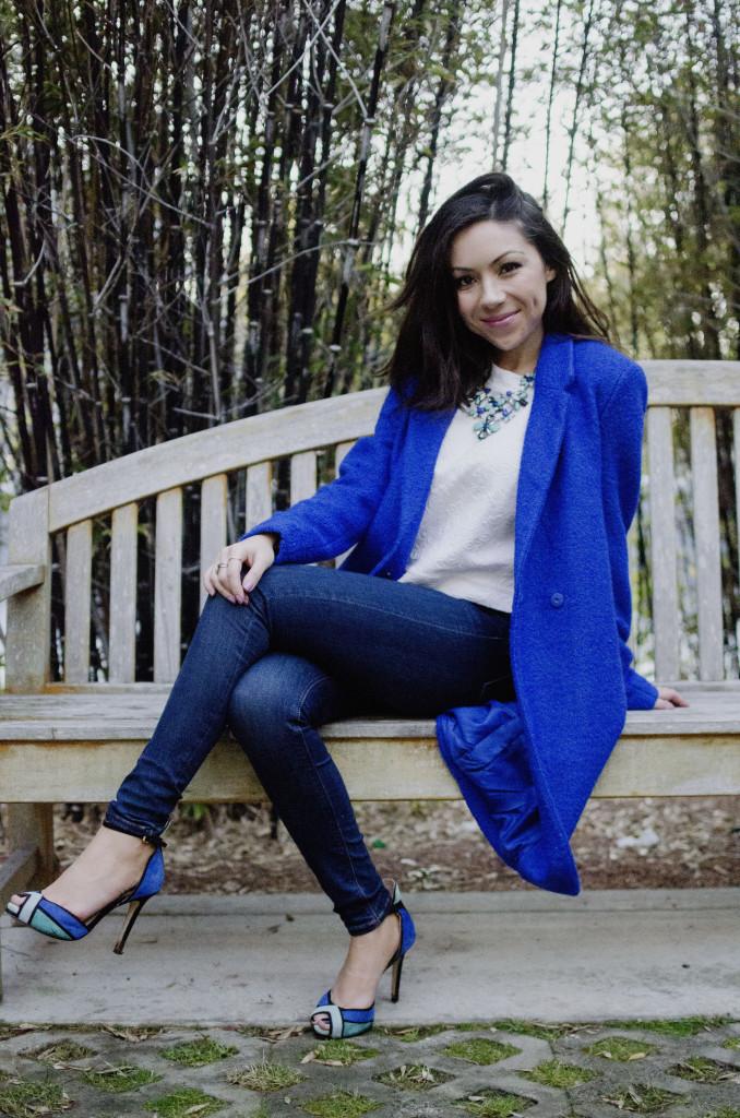 Nihan Gorkem wearing a blue coat sitting on a bench