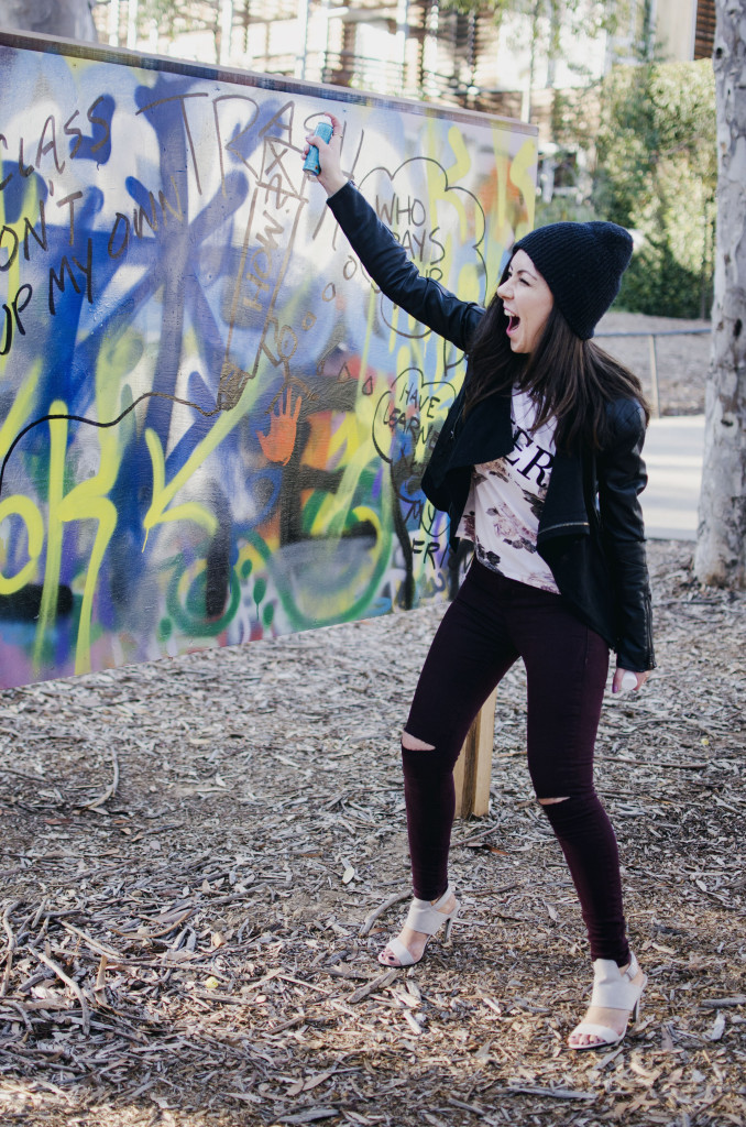 Model painting on a graffiti wall and showing her outfit
