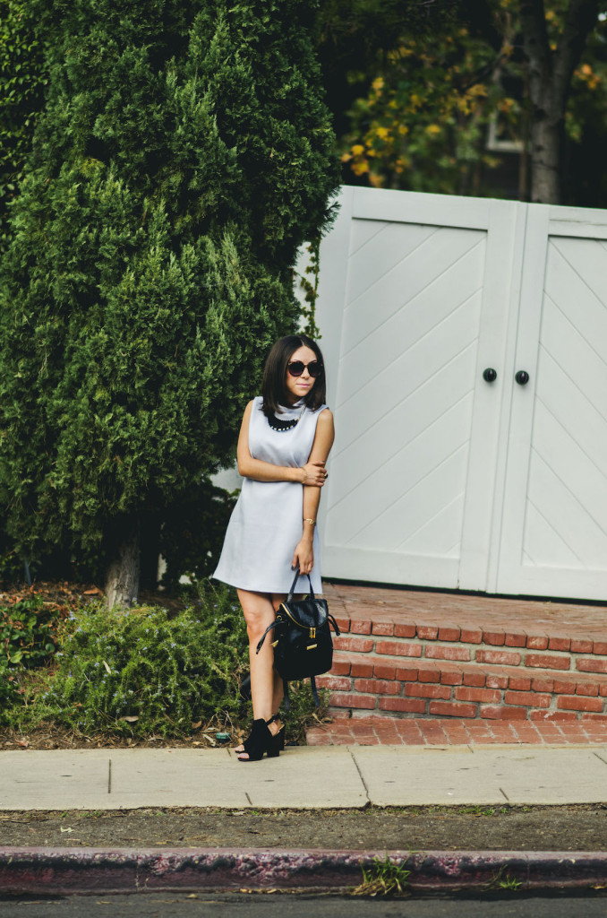 Nihan Gorkem wearing baby blue mod dress black and gold backpack black open toe booties and jewelry, posing in front of a cute white door - - winter baby blues