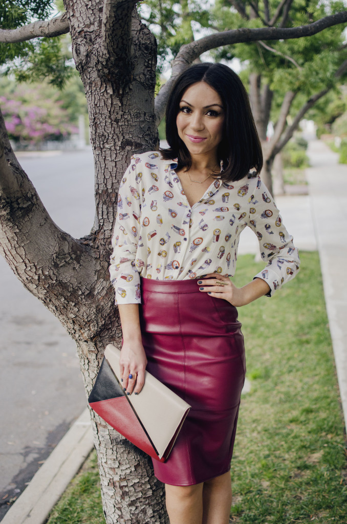 Blogger Nihan leaning on a tree, wearing a Zara owly shirt, Asos leather skirt and Asos colorblock clutch