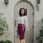 Blogger Nihan Gorkem standing by a cute door, wearing a Zara owly shirt, Asos leather skirt, black strappy Topshop high-heels and Asos colorblock clutch