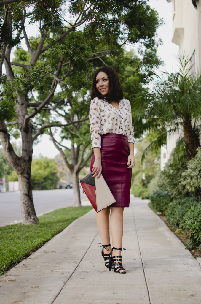 Blogger Nihan Gorkem standing and looking to her right, wearing a Zara owly shirt, Asos leather skirt, black strappy Topshop high-heels  and Lulu's oversized navy coat and Asos colorblock clutch