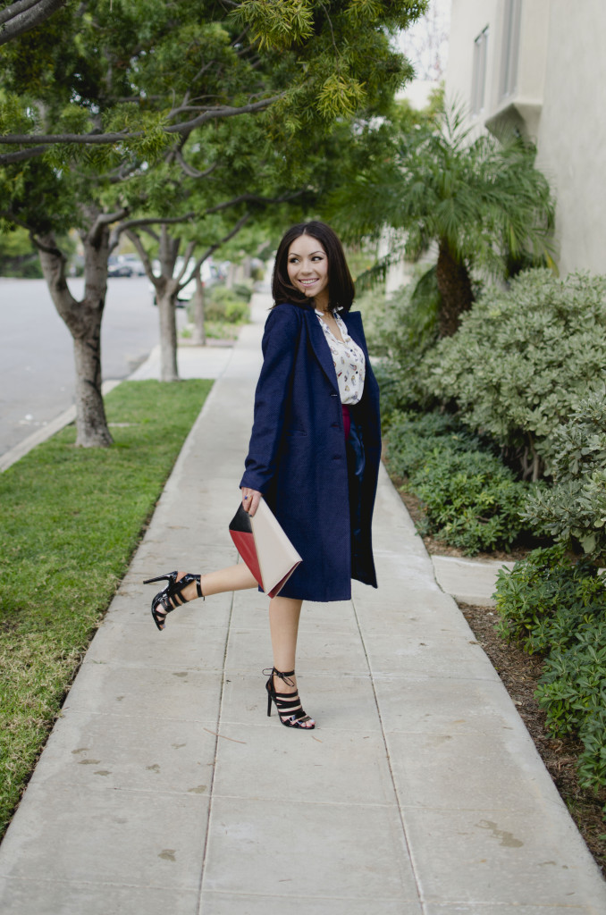 Blogger Nihan Gorkem standing on a cute street, wearing a Zara owly shirt, Asos leather skirt, black strappy Topshop high-heels  and Lulu's oversized navy coat and Asos color block clutch