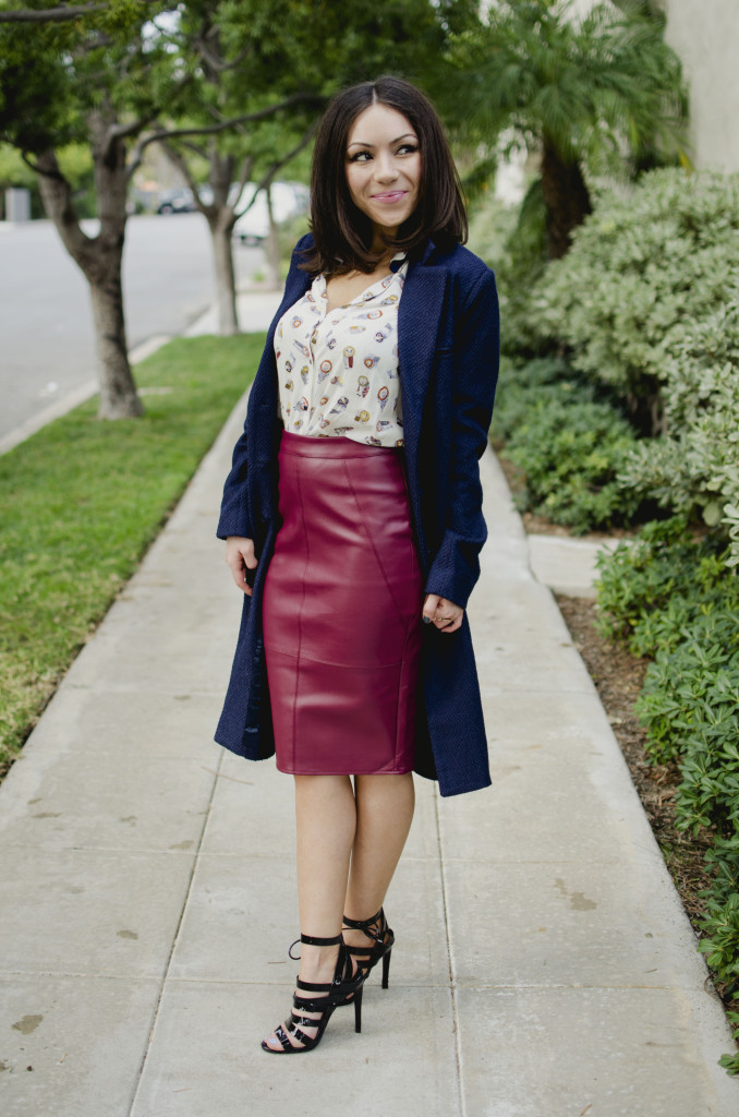 Blogger Nihan Gorkem standing and posing, wearing a Zara owly shirt, Asos leather skirt, black strappy Topshop high-heels  and Lulu's oversized navy coat and Asos color block clutch