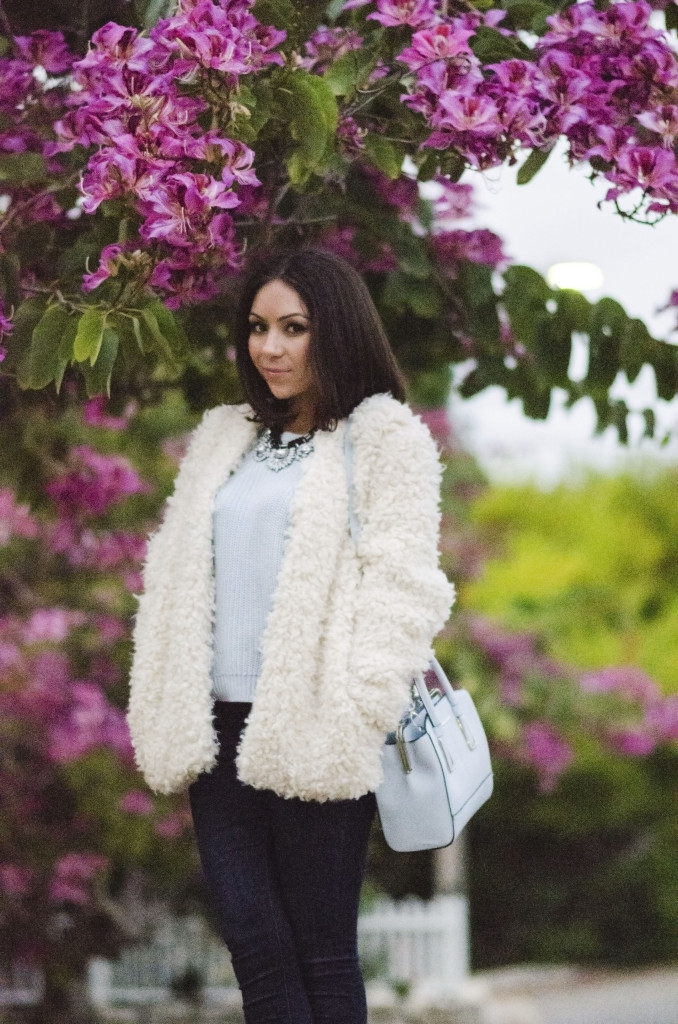 Nihan posing in front of pink gorgeous flowers, showing her outfit and fur coat
