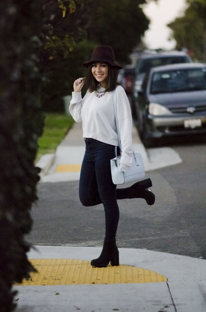 Nihan smiling and posing in Bird Rock San Diego, wearing a Topshop white sweatshirt, Topshop skinny jeans and River Island Blue Tote Bag