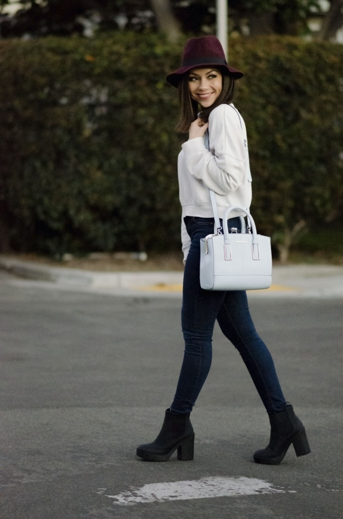 Nihan walking on the street showing her blue River island bag, Topshop jeans and a white Topshop sweathirt