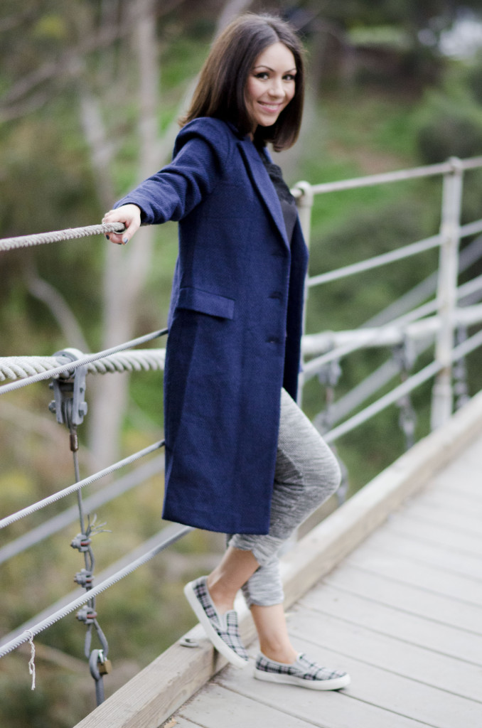 Nihan wearing sweatpants, and a blue long coat at bridge