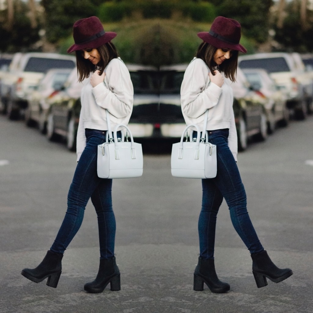 Nihan walking on the street wearing a white Topshop sweatshirt, blue jeans and a red fedora hat