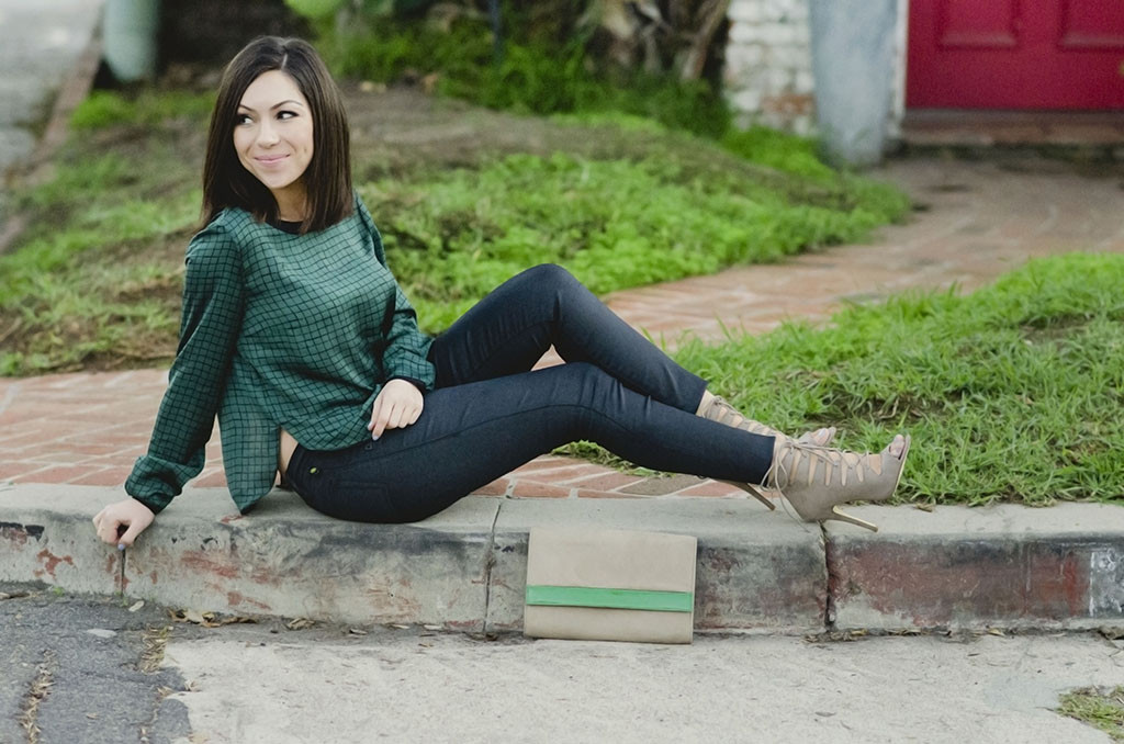 Blogger Nihan showing her green top, black pants and nude high-heels while sitting on pavement