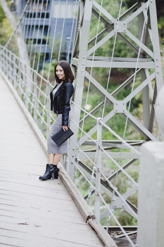 Blogger Nihan wearing Topshop grey midi skirt, grey top , black boots and leather Topshop jacket at the Suspension Bridge in San Diego