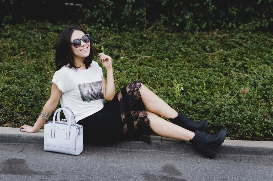 Fashion blogger Nihan posing in her look of the day. Black lace Topshop midi skirt , a white t-shirt and blue structured purse from River Island