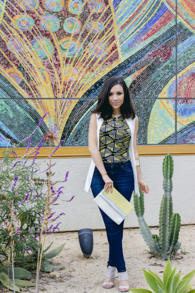 Nihan Gorkem posing in a cactus garden wearing a Topshop white sleeveless jacket, Topshop printed top, blue high-waisted jeans and a colorblock clutch from H&M