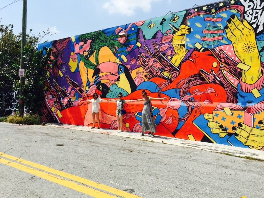 Nihan and friends posing in front a mural in Wynwood Walls, Miami