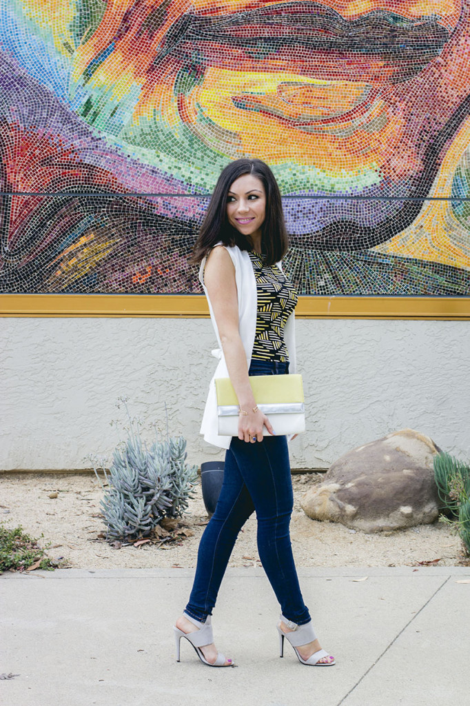 Nihan posing in front a mural wearing a Topshop white sleeveless jacket, Topshop printed top, blue high-waisted jeans and a colorblock clutch