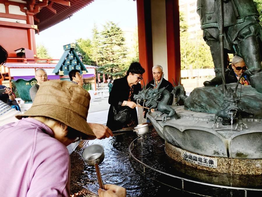 People drinking sacred water Sensoji asakusa buddhist temple