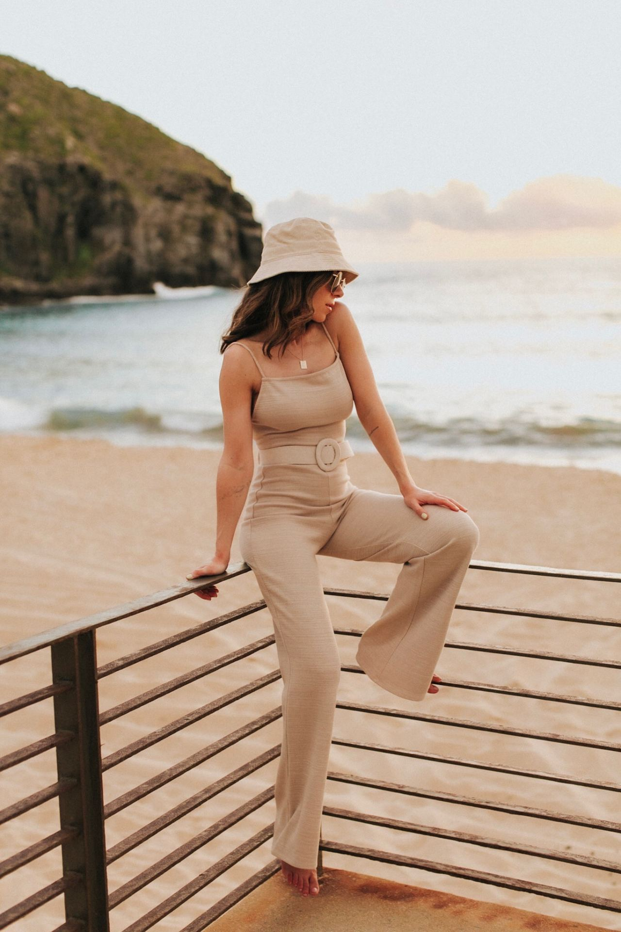 Travel Blogger Nihan Gorkem wearing Lovers and Friends beige jumpsuit and H&M Bucket Bag