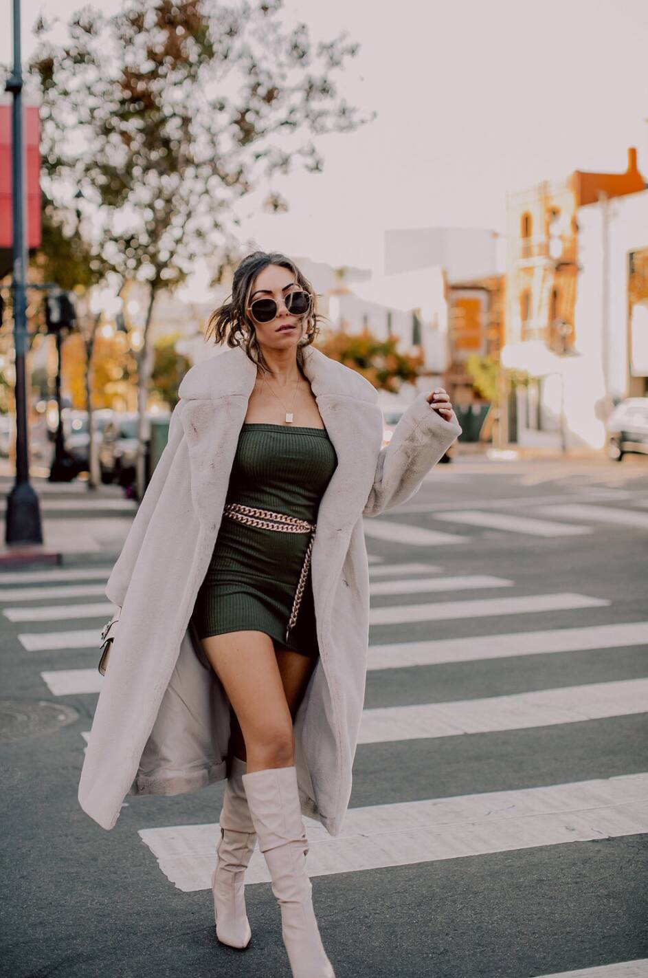 Style blogger wearing Revolve mini knit dress, HM faux fur coat and Public Desire knee high boots