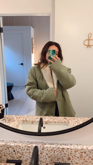 Travel Blogger Nihan wearing Tularosa coat at White Water Cambria deluxe king room
